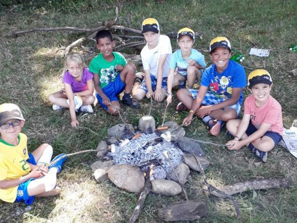 Grilling sausages over an open fire at Kids Camp